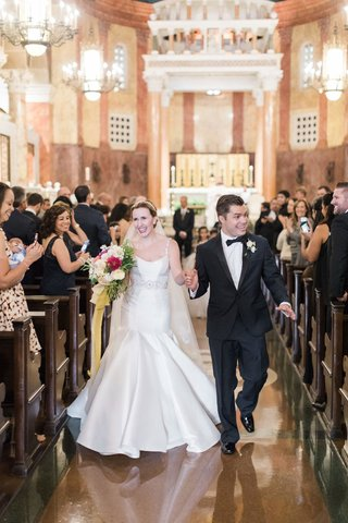 bride-in-trumpet-wedding-dress-with-groom-in-tuxedo-bow-tie-church-pews-wedding-guests-with-phones