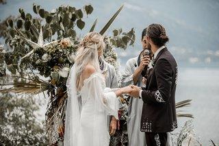 bride-and-groom-at-boho-chic-wedding-ceremony-lake-como-star-decor-palm-protea-flowers