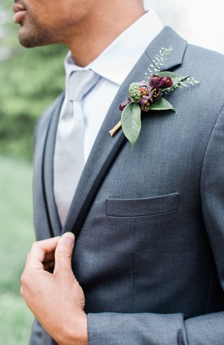 boutonniere-with-dark-burgundy-blooms-and-green-leaves