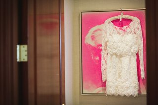 second-wedding-dress-hanging-on-pink-painting-white-lace-long-sleeve-scallop-hem-short-dress