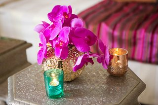 moroccan-themed-engagement-party-silver-table-with-golden-vase-hot-pink-orchids-votive-candles