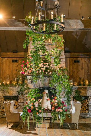wedding-reception-stone-fireplace-greenery-cake-swing-with-flowers-greens-hovering-off-ground