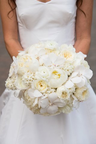 bride-holding-bouquet-with-orchids-ranunculus-peonies-and-additional-white-blooms