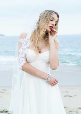 bride-on-beach-in-strapless-wedding-dress-with-pretty-bracelet-and-lace-trim-veil-dark-lipstick
