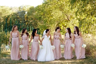 bride-in-lace-gown-and-veil-with-bridesmaids-in-long-pink-dresses-with-brown-sashes-white-bouquet