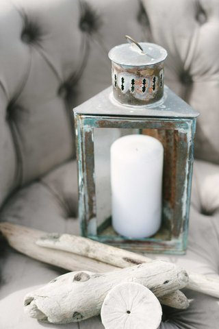a-chipped-blue-and-gray-lantern-with-a-white-candle-pieces-of-driftwood-sand-dollar-on-gray-chair
