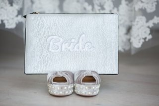 wedding-clutch-on-top-of-silver-shoes-silver-leather-clutch-pouch-with-bride-embroidery-detailing