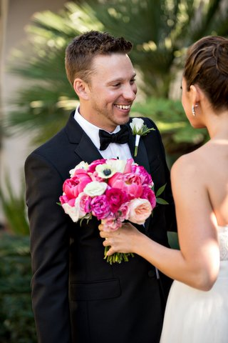groom-smiles-at-bride-during-first-look-before-wedding-ceremony