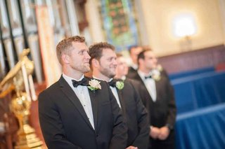 brian-leonard-running-back-in-a-black-tuxedo-with-peach-rose-boutonniere-at-his-wedding-ceremony