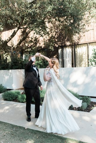 bride-in-jinza-couture-bridal-gown-groom-twirls-bride-during-first-look