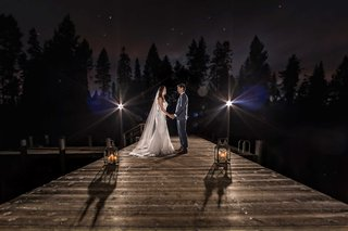 couple-on-dock-night-dusk-small-lights-darkened-background-lake-tahoe-california
