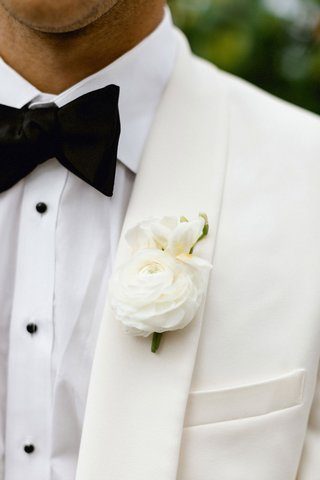 wedding-attire-for-groom-white-suitsupply-tux-with-black-bow-tie-white-ranunculus-flower-boutonniere