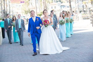 bride-and-groom-walk-down-smiling-with-bridesmaids-and-groomsmen-in-back