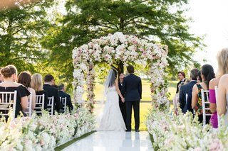 bride-in-monique-lhuillier-wedding-dress-under-flower-arch-groom-white-aisle-runner-pink-ivory-color