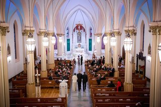 catholic-wedding-ceremony-with-groom-in-black-tuxedo-being-walked-down-aisle-by-parents-our-lady-of