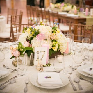 watercolor-table-numbers-with-low-floral-centerpieces-and-colorful-candles-in-hurricances
