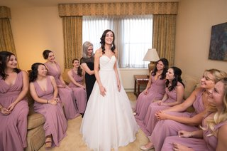 bride-in-essence-of-australia-wedding-dress-mother-of-the-bride-helps-with-dress-bridesmaids-watch