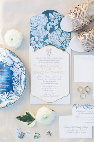 wedding-invitation-with-white-flowers-on-blue-background-gold-border-calligraphy-monogram