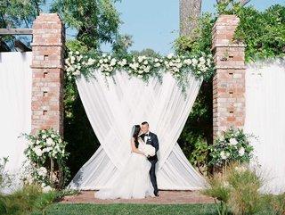 wedding-ceremony-white-drapes-bride-groom-portrait-altar-greenery-white-pink-flowers