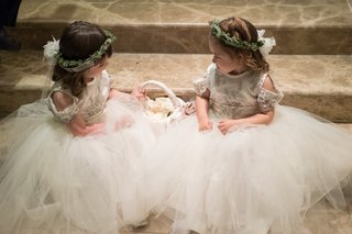 flower-girls-with-tulle-skirts-greenery-crown-sitting-on-steps-before-ceremony