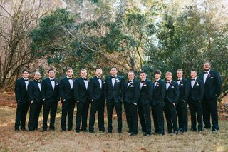 groom-with-groomsmen-wearing-suits-and-bow-ties-red-boutonniere-holiday-wedding