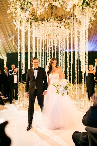 bride-in-monique-lhuillier-wedding-dress-holding-bouquet-neutral-with-groom-after-ceremony-tent