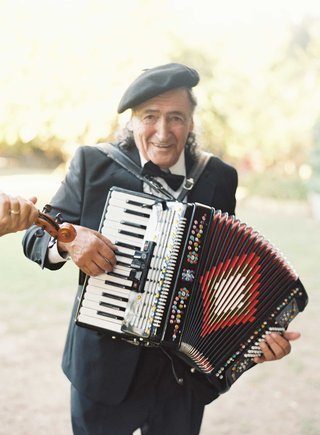 man-in-paris-theme-beret-playing-accordion-at-chic-outdoor-wedding-in-malibu