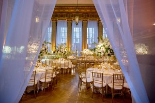wedding-reception-drapery-at-entrance-tall-ceilings-windows-white-tables-gold-chairs-tall-flowers