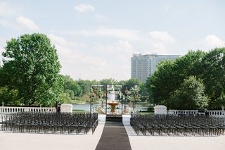 A Charming Fete Unique Ceremony chandelier black chairs fountain backdrop