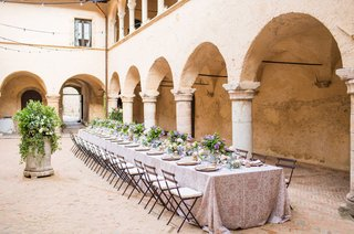 wedding-reception-courtyard-italy-destination-wedding-reception-low-centerpiece-arch-pillars-bistro