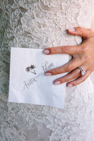 bride-in-an-alencon-lace-dress-diamond-rings-holds-cocktail-napkin-with-bride-grooms-names