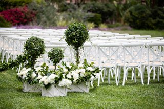 wedding ceremony on lawn x back white guest chairs planters with hydrangea rose and greenery boxwood round
