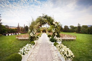 wedding-ceremony-archway-of-greenery-boxwood-white-flower-boxes-wood-aisle-runner-chairs-green-lawn