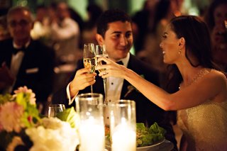 bride-and-groom-look-into-each-others-eyes-and-cheers-clink-glasses-at-wedding-reception-toast