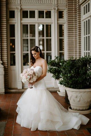 bride-in-strapless-wedding-dress-horsehair-trim-pink-bouquet-large-headpiece