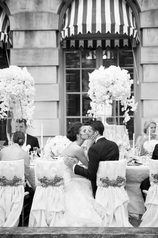 black-and-white-photo-of-wedding-reception-bride-and-groom-kissing-at-chairs-nuage-designs-interlace