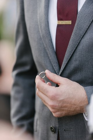 groom-in-grey-suit-and-burgundy-tie-holding-wedding-ring-during-ceremony