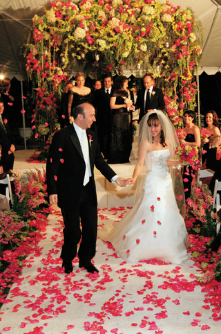 bride-and-groom-in-front-of-flower-chuppah-at-nighttime-wedding-ceremony