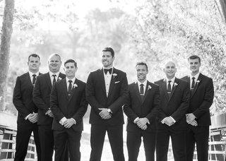 black-and-white-photo-of-groom-with-groomsmen-in-tuxedos-on-bridge