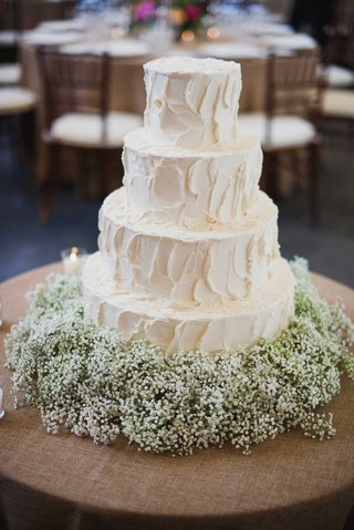simple-white-four-layer-wedding-cake-with-babys-breath-flowers-at-base