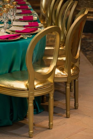 gold-shiny-cushioned-chairs-at-bold-blue-linens-with-bright-pink-napkins