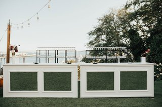 outdoor-wedding-reception-cocktail-hour-white-mirror-hedge-bar-greenery-shelving-string-bistro-light