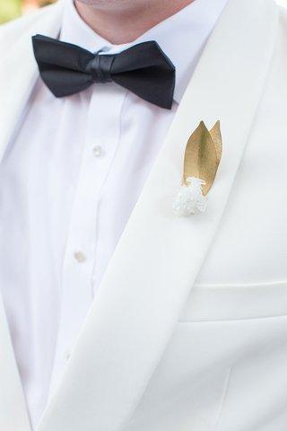 gold-leaf-and-quartz-wedding-boutonniere-on-ivory-suit-jacket-black-bow-tie