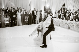 black-and-white-photo-of-first-dance-groom-dipping-bride-while-guests-clap-and-watch-live-band