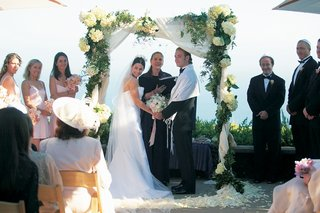bride-and-groom-under-white-and-green-altar
