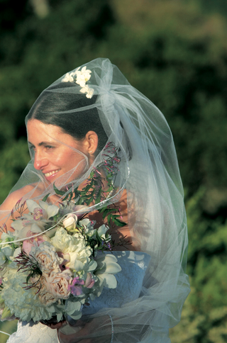 bride-holding-bouquet-with-veil-covering-face