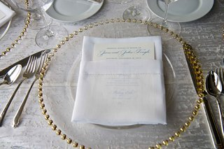 wedding-reception-place-setting-with-clear-glass-gold-beaded-charger-menu-with-blue-print-in-napkin