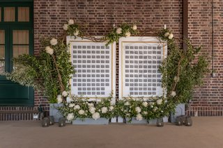 grey-escort-cards-framed-by-gold-and-surrounded-by-greenery-and-white-flowers