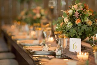 wedding-reception-long-wood-table-with-lace-napkin-details-gold-rim-goblet-table-number-low-flowers