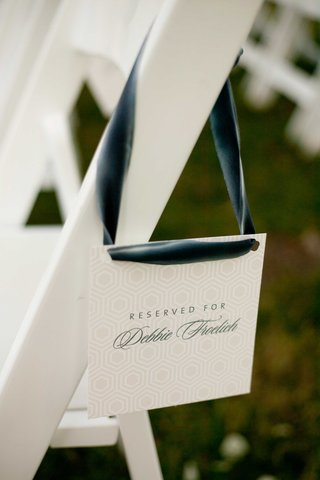 white-cards-with-blue-and-gray-lettering-reserve-a-seat-at-wedding-ceremony